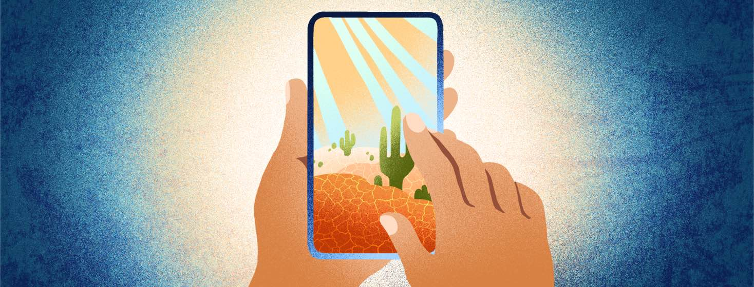 A person's hands hold a smartphone, which shows a dry desert on the screen.