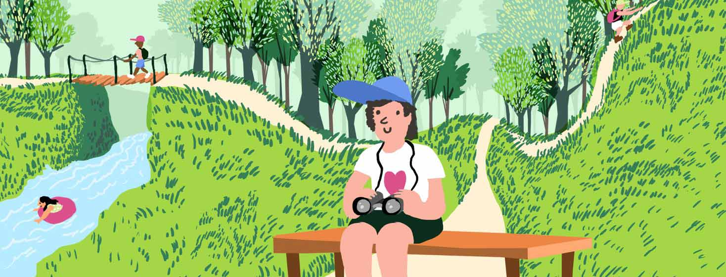 A person smiling on a bench with binoculars in a lush park where people are enjoying outdoor activities.